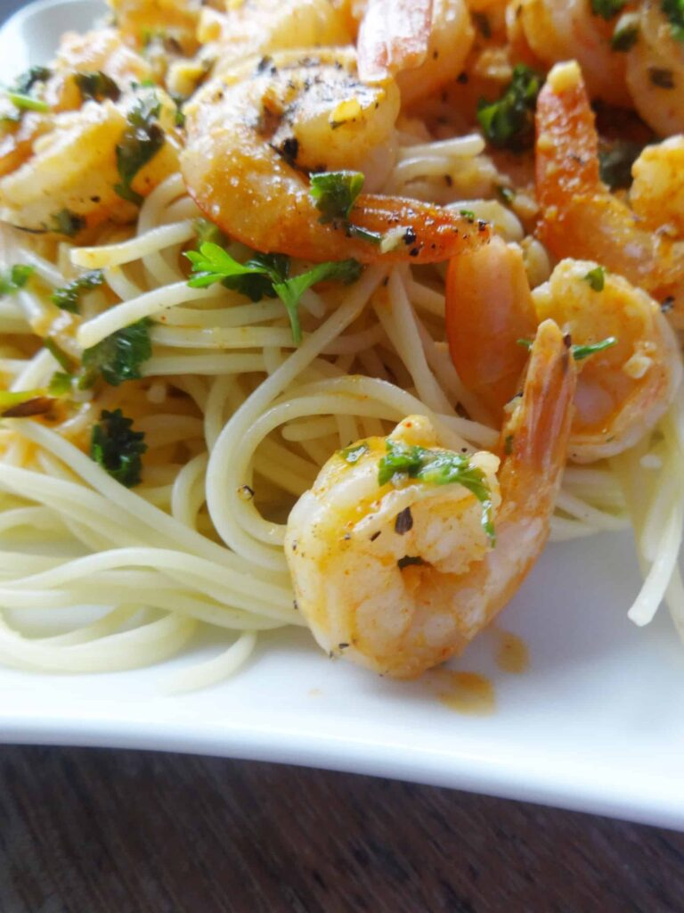 Tail-on shrimp served over pasta